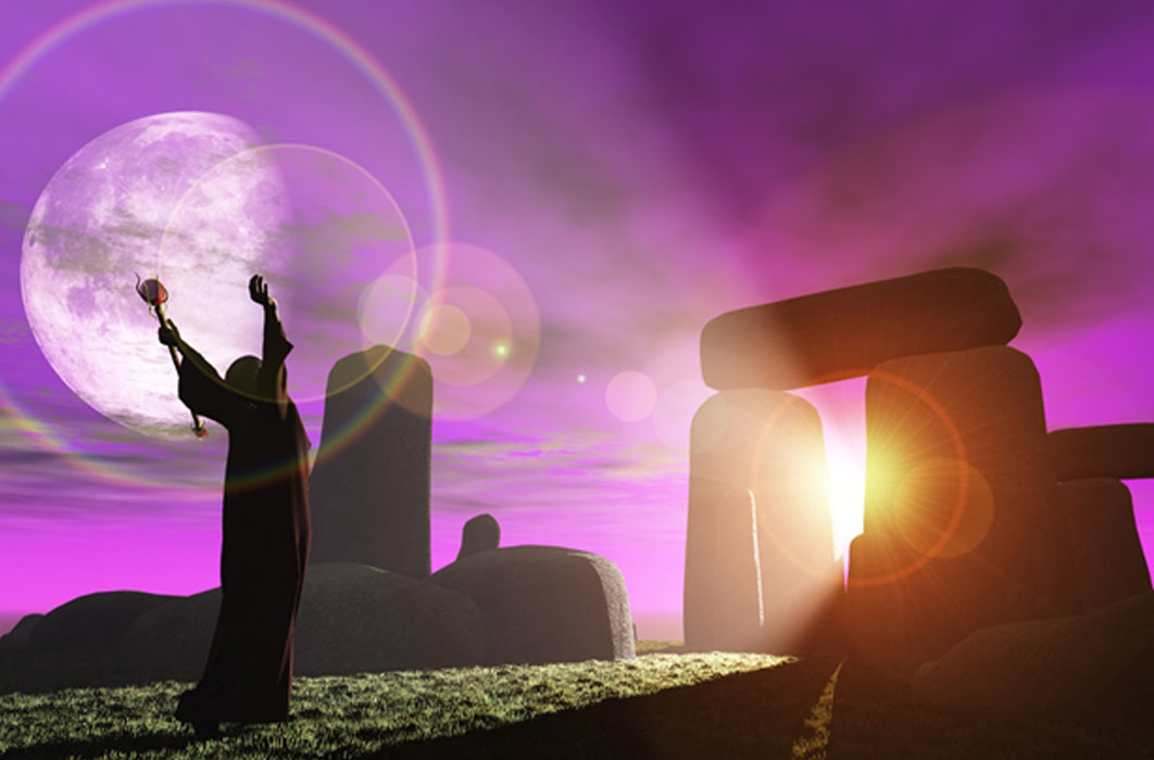 Druid greets the dawn at Stonehenge (heywoody  / adobe stock)