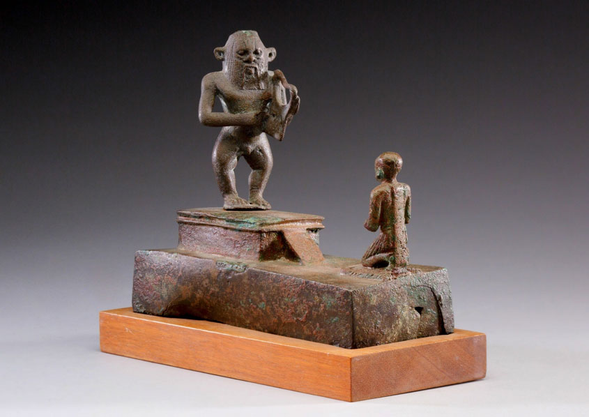 Bes was worshipped and invoked by ordinary Egyptians as a protector. His usual depiction, as a grotesque dwarf with a lion's ears and mane, was thought to deter the approach of the malevolent forces believed to cause illness. His image here appears in a bronze statuette made for the unnamed man shown worshipping the god. The harp held by Bes may reflect his power to calm angry spirits. Bronze or copper alloy. Late Period, Dynasty 26–29. Metropolitan Museum of Art, New York.