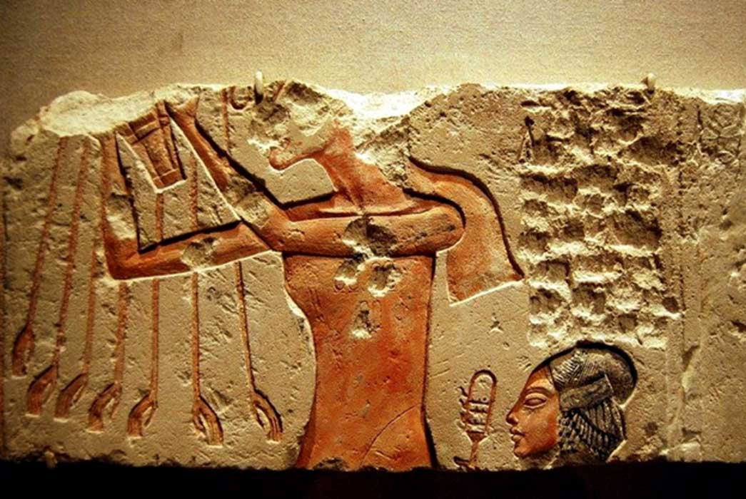 Painted limestone block from Amarna shows Akhenaten worshipping the Aten; while his daughter, Meritaten, shakes a sistrum; design by Anand Balaji (Photo credit: Brooklyn Museum, New York); Deriv.