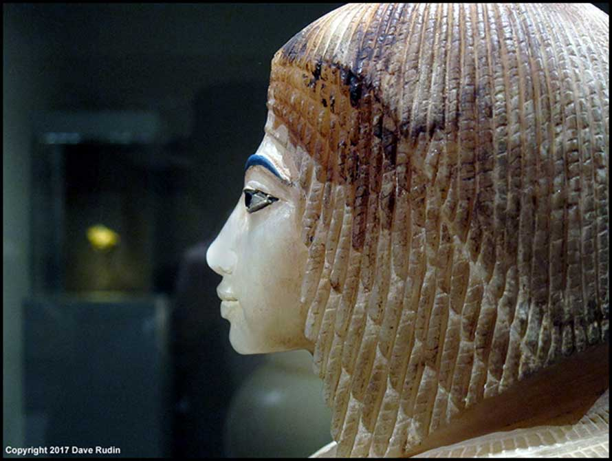 "One of the four elegant canopic jar stoppers made of Egyptian alabaster that was discovered in a niche in Tomb 55. It represents a royal lady wearing the Nubian wig. The uraeus was snapped off and the inscriptions on the jar erased in antiquity, but experts reconstructed the name ""Kiya"". Davis/Ayrton excavations, 1907. Metropolitan Museum of Art, New York."