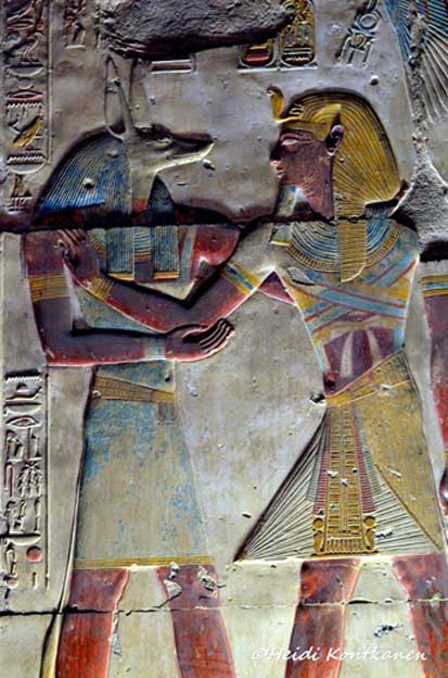 This relief shows Wepwawet embracing Seti I as the King journeys to the Next World; the vulture goddess Nekhbet hovers above protectively (top right). The scene is found on the western wall of the Second Hypostyle Hall; between the chapels of Isis and Osiris. Mortuary Temple of Seti I, Abydos.