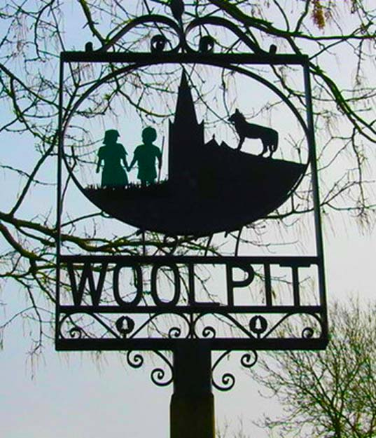 Woolpit village sign featuring two green children and a wolf (commissioned 1977)