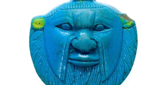 Faience amulet of the head of Bes from the Late Period, 26th to 30th Dynasties. The deity was worshipped and invoked by ordinary Egyptians as a protector against malevolent forces; design by Anand Balaji